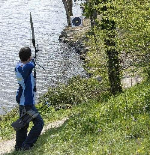 Archer en position de tir sur un parcours campagne